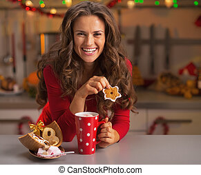 Happy young woman in red dress having snack in christmas...