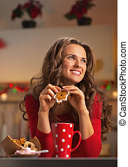 Thoughtful young woman in red dress having snack in...