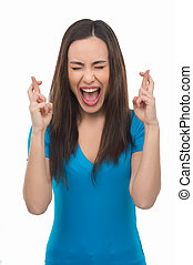 Fingers crossed. Happy young woman with closed eyes holding her fingers crossed while standing isolated on white