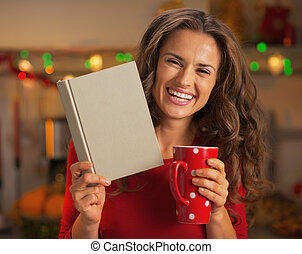 Happy young woman with cup of hot chocolate reading book in...