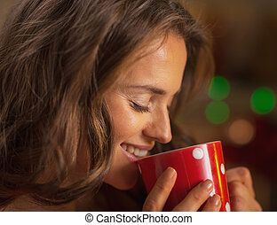 Portrait of happy young woman drinking hot chocolate