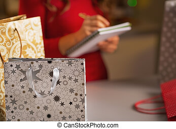 Closeup on christmas shopping bag and woman checking list of...