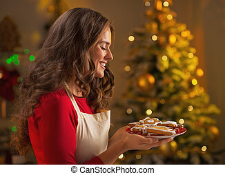 Happy young housewife showing christmas cookies