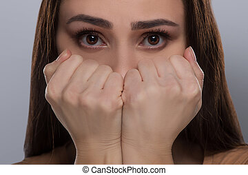 Scared woman. Terrified young woman covering mouth with...