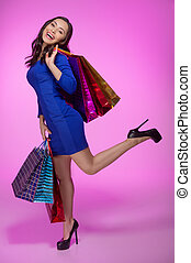 Woman with shopping bags. Full length of cheerful young woman holding shopping bags and smiling at camera while standing isolated on colored background