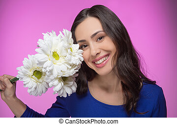 Beauty with flowers. Portrait of beautiful young woman...