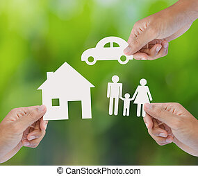 a paper home, car, family - Hand holding a paper home, car,...
