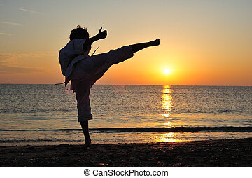 Martial art - Young boy in karate uniform training at sunset