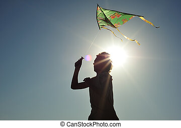 Kite flying - Young boy running and flying a kite