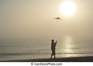 Flying kite - Boy flying a kite on beach at sunrise