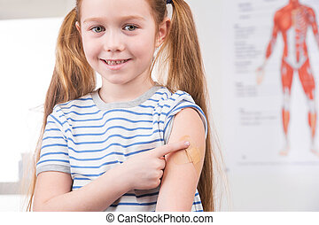 Vaccination. Cheerful little girl holding finger on the arm...