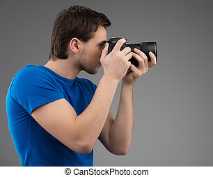 Man with camera. Side view of confident young man holding...