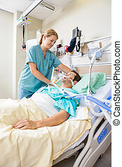 Nurse Adjusting Patients Pillow - Friendly nurse adjusting...