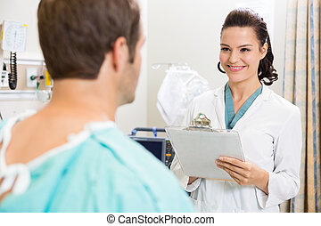 Doctor With Clipboard Examining Patient's Medical Report