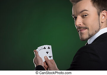 Man with cards. Cheerful young man in formalwear holding...