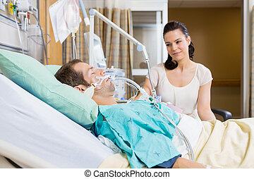 Woman Looking At Man In Hospital - Beautiful woman looking...