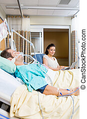 Woman With Laptop Sitting By Patient In Hospital - Portrait...