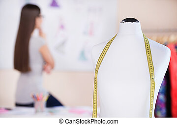 Fashion designer at work. Rear view of beautiful young woman looking at her sketches and holding hand on chin