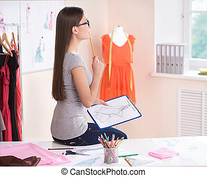 Fashion designer at work. Side view of beautiful young woman at fashion design studio