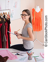 Fashion designer at work. Side view of cheerful young woman at fashion design studio