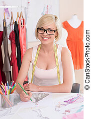 Fashion designer at work. Cheerful young fashion designer drawing sketch and smiling