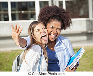 Playful Student With Friend Making Facial Expressions On...
