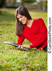 Student Reading Book While Relaxing On Grass At Campus -...