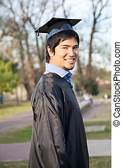 Happy Man In Graduation Gown On University Campus