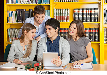 College Friends With Digital Tablet Studying In Library -...