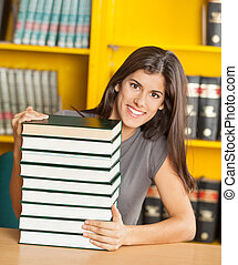 Student With Piled Books Sitting At Table In Library