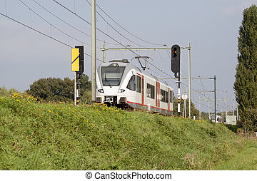 Train travels over a small dike in Limburg, Netherlands