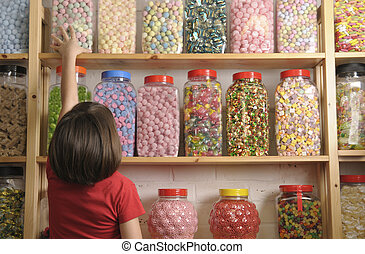 child in sweet shop - child reaching for sweet jar on top...