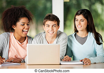 Student With Friends Looking At Laptop In Classroom -...