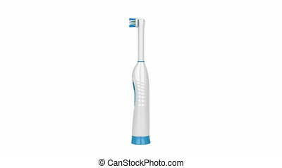 Electric toothbrush rotates on white background