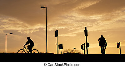 silhouette of city on sunset with cyclist