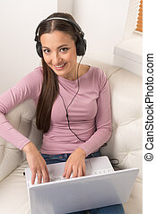 Women with laptop. Top view of cheerful young women in headphones working at the computer while sitting on the couch