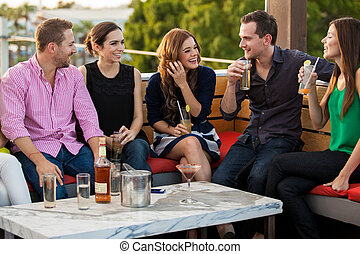 Young adults having drinks at a bar