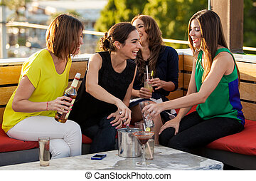 Cute female friends having drinks - Group of four female...