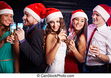 Christmas party - Company of friends in Santa caps holding...