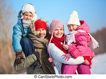 Winter family - Happy parents with kids in winterwear...