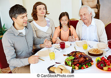 Giving thanks to God - Portrait of family of four sitting at...