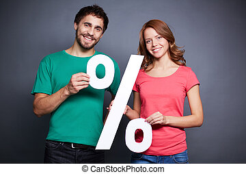 Announcing discount - Portrait of young couple holding paper...