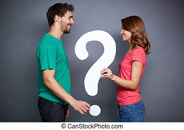 Big question - Portrait of young couple holding paper...