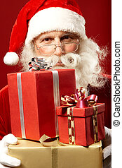 Generous Santa - Photo of Santa Claus with giftboxes looking...