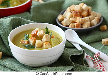 Creamy sweet potato soup with croutons and parsley in white...
