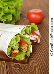 wheat tortilla with chicken and vegetables on wood board
