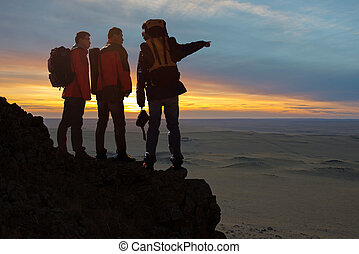 Three travelers - 3 tourists with backpacks relaxing on top...
