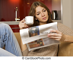 mid adult woman drinking coffee and reading news