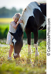 Child and horse in filed - Child with horse outdoor at...