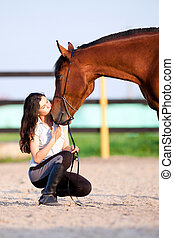 Young girl with bay horse - kiss